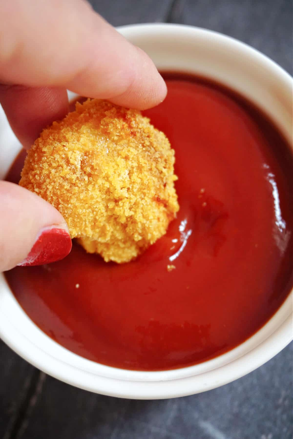 A chicken nugget being dipped in ketchup