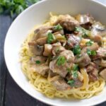 A white plate with beef stroganoff over noodles
