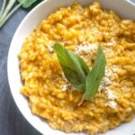 A white bowl with pumpkin risotto garnished with fresh sage leaves and grated parmesan
