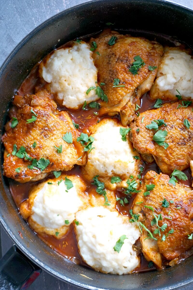 A pan with chicken paprikash and dumplings garnished with parsley