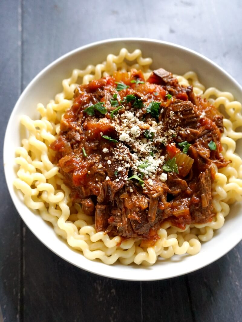 A white plate with pasta and shredded beef ragu