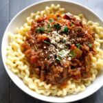 A white plate with shredded beef ragu over pasta