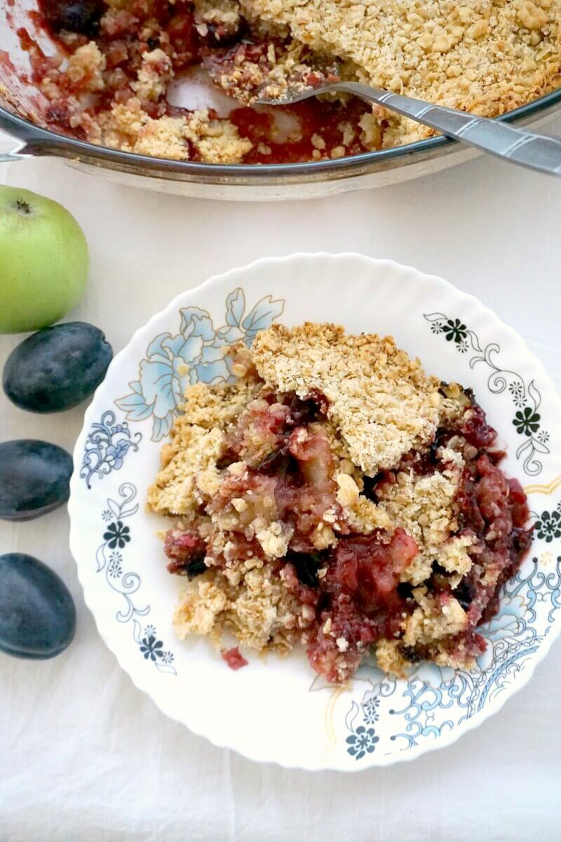 Overhead shoot of a white and blue plate with apple and plum crumble