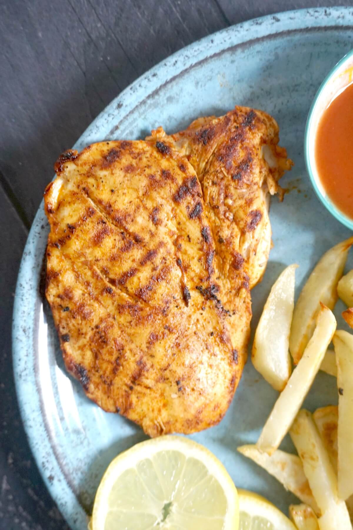 Close-up shoot of a butteflied chicken breast on a blue plate with chips and a sauce in a small bowl