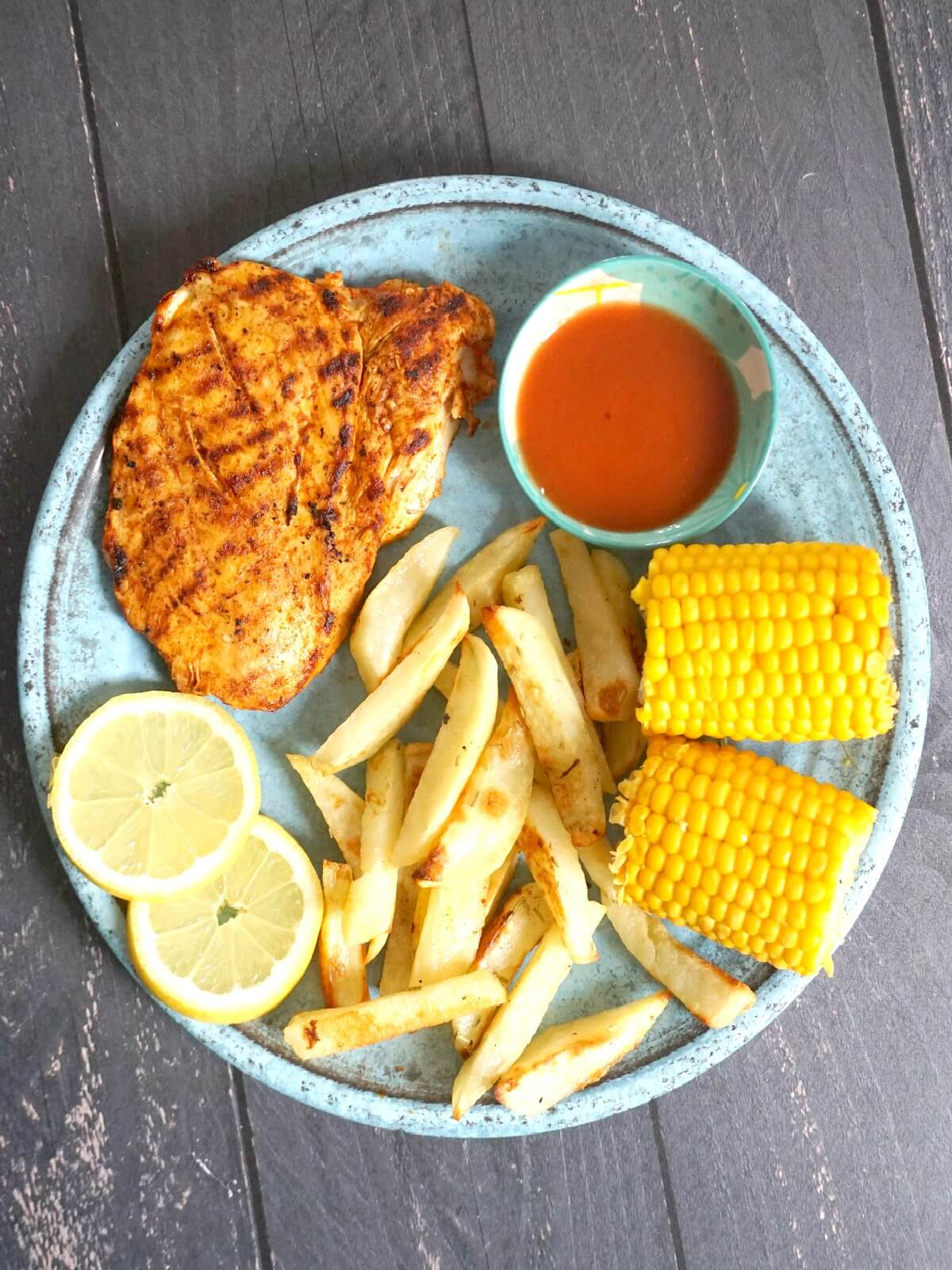 Overhead shoot of a blue plate with chicken breast, chips, 2 corns on the cob, 2 lemon slices and chilli sauce