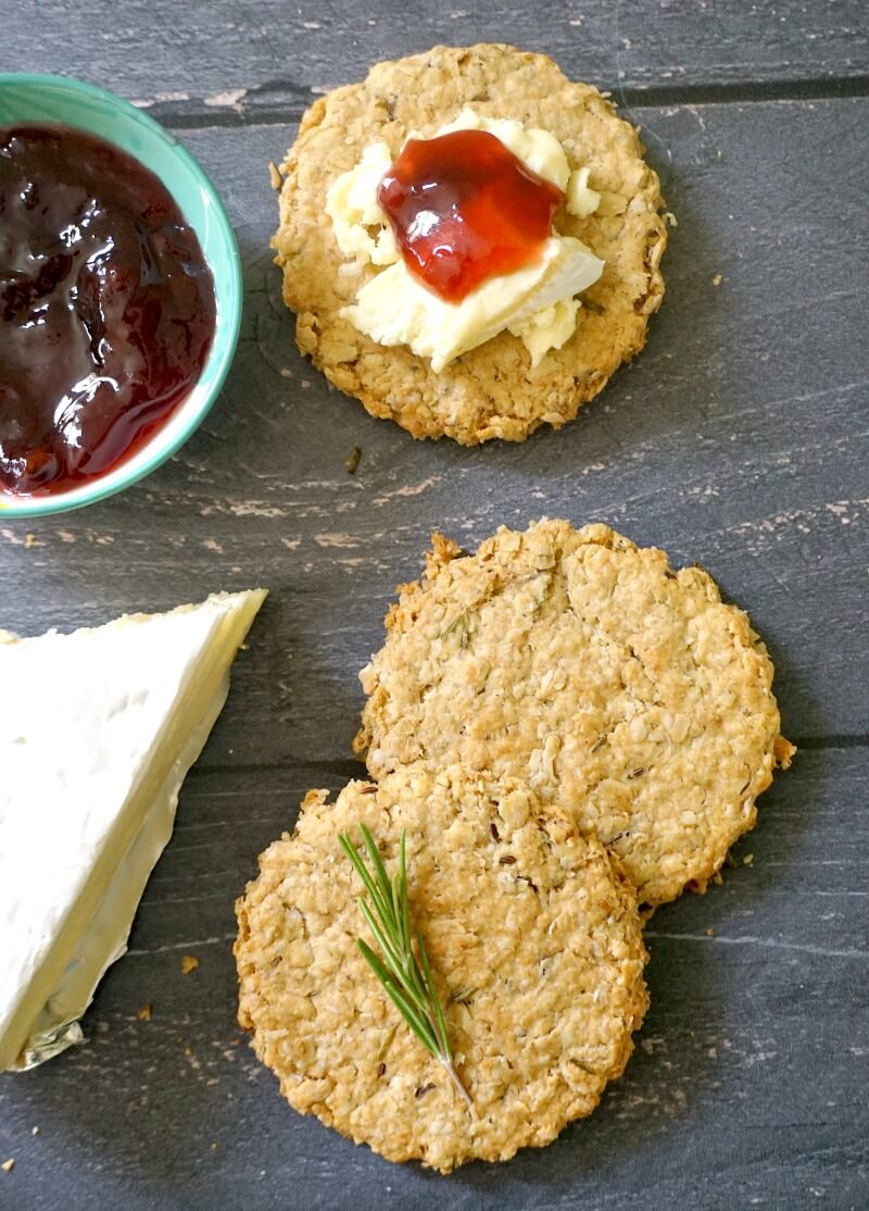 Overhead shoot of 2 oat biscuits a wedge of cheese, a small bowl of jam and a cookie topped with cheese and jam
