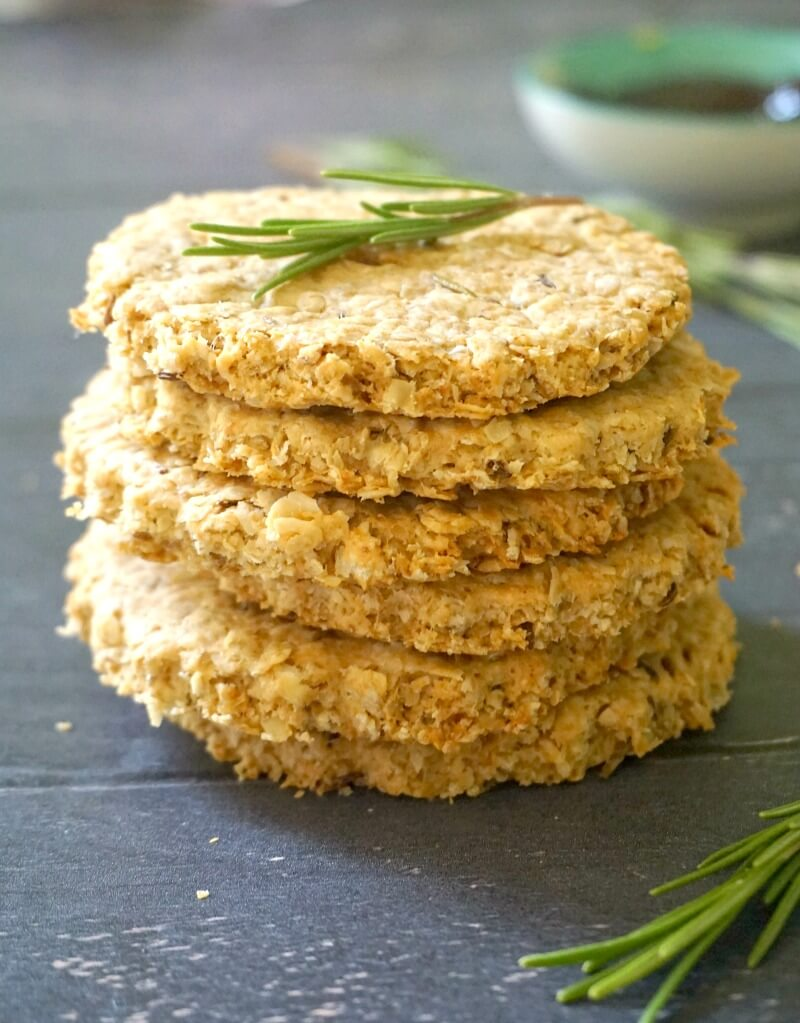 A stack of 6 oarmeal cookies with a small resemary sprig on top