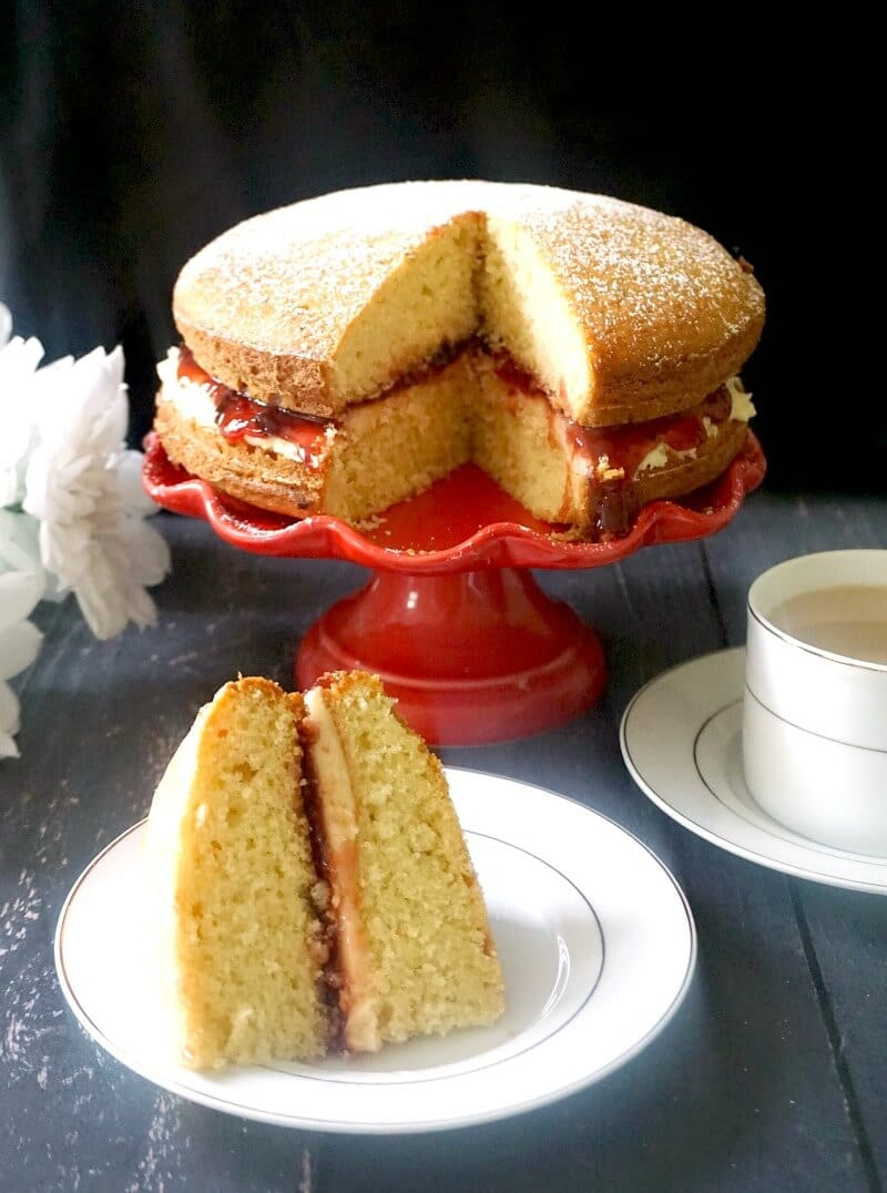 A slice of Victoria Sponge Cake on a white plate, a red cake stand with more cake and a cup of tea on the side