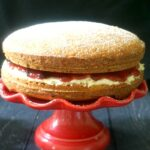 A red cake stand with a Victoria Sponge Cake on it