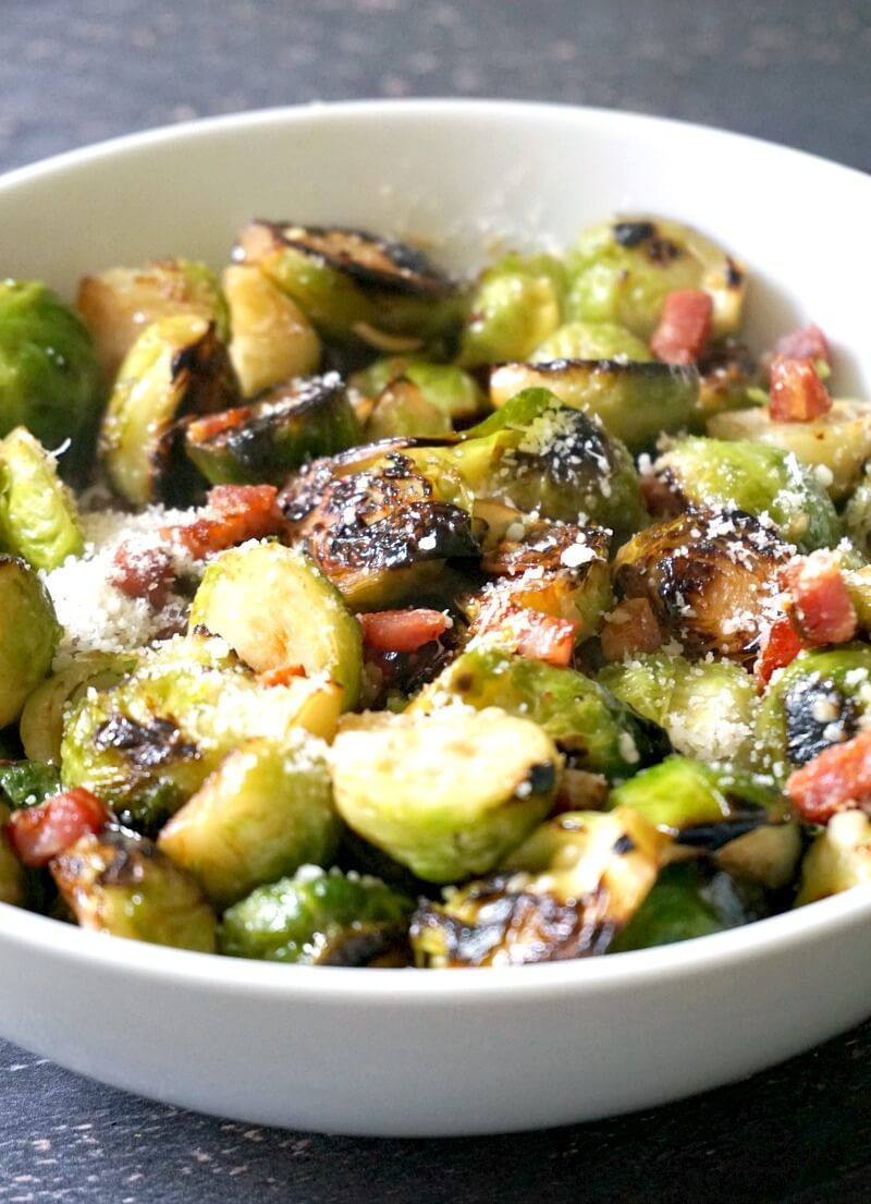 A white bowl with sauteed brussels sprouts, bacon and parmesan