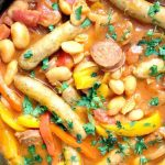 Sausage and Butter Bean Casserole, a hearty dish for an epic family dinner. Made with chipolatas sausages, chorizo, butter beans, and peppers, simmered in a rich tomato sauce, this simple sausage casserole is a big hit every single time. That's what I call comfort food! My sausage and bean casserole can be enjoyed by the whole family no matter the season, it's hearty and filling, but so so nutritious and delicious. #casserole, #sausagebeancasserole, #comfortfood, #chorizo, #chipolatassausages