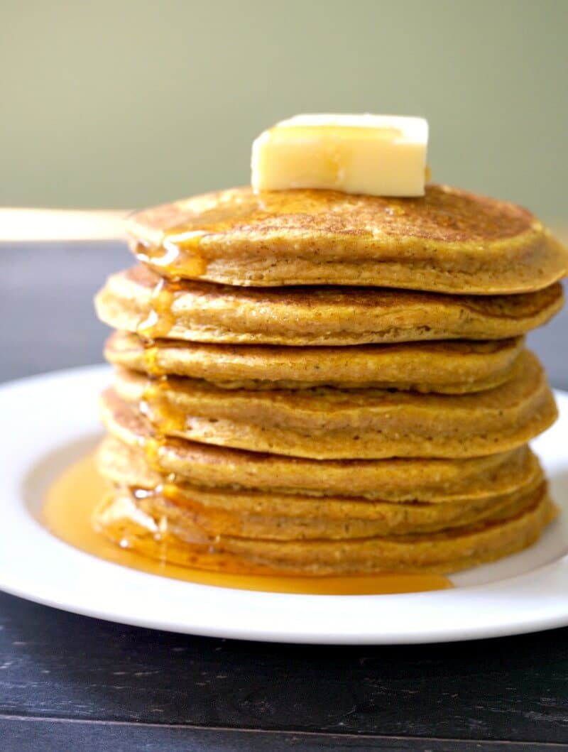 A stack of 7 oatmeal pumpkin pancakes with butter on top and maple syrup