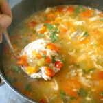 A pot of turkey rice soup with a ladle inside