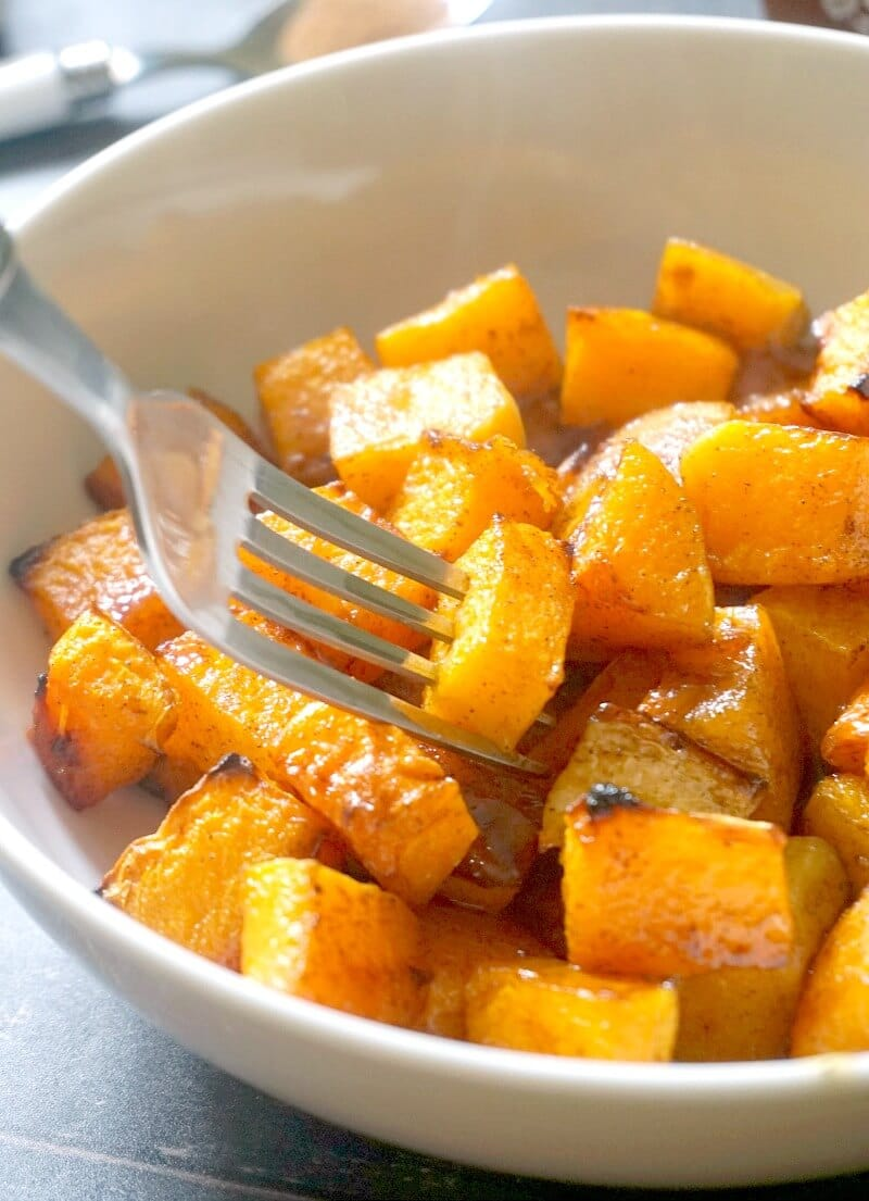A white bowl with roasted butternut squash with maple syrup and cinnamon and a fork