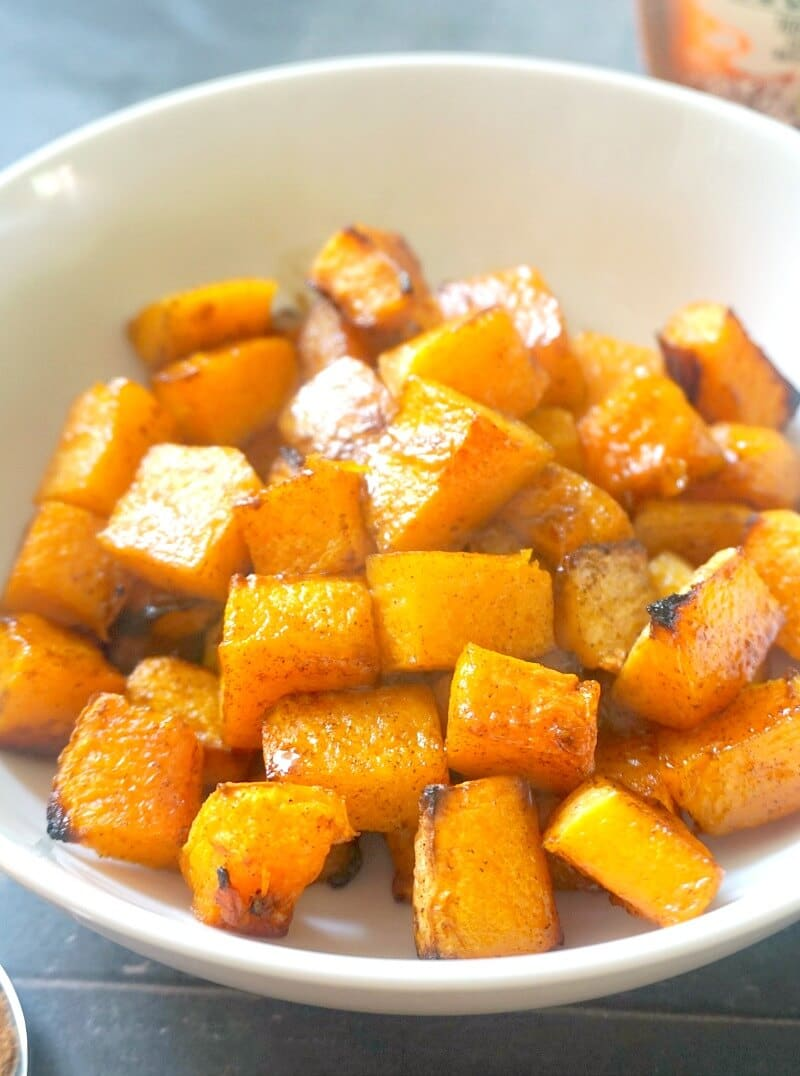 A white bowl with roasted butternut squash cubes