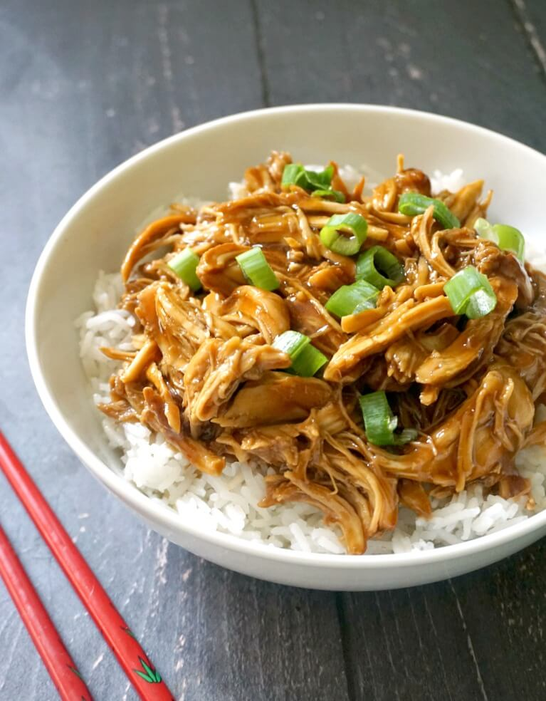 A white bowl with rice and shredded chicken teriyaki topped with chopped spring onions
