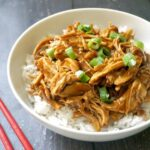 A white bowl of shredded teriyaki chicken over a bed of rice