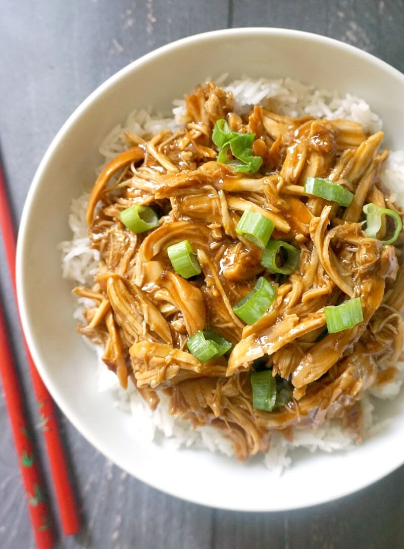 Overhead shoot of a white bowl with rice, shredded chicken teriyaki garnished with chopped spring onions
