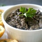 A white pot of tapenade with parsely leaves on top
