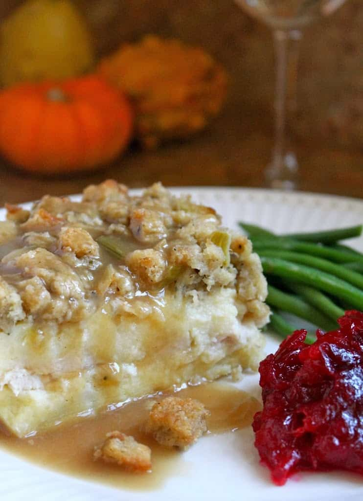 A slice of potato, turkey and stuffing layered leftovers on a white plate with a dollop of cranberry sauce and green beans