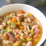 A white bowl with leftover ham and bean soup