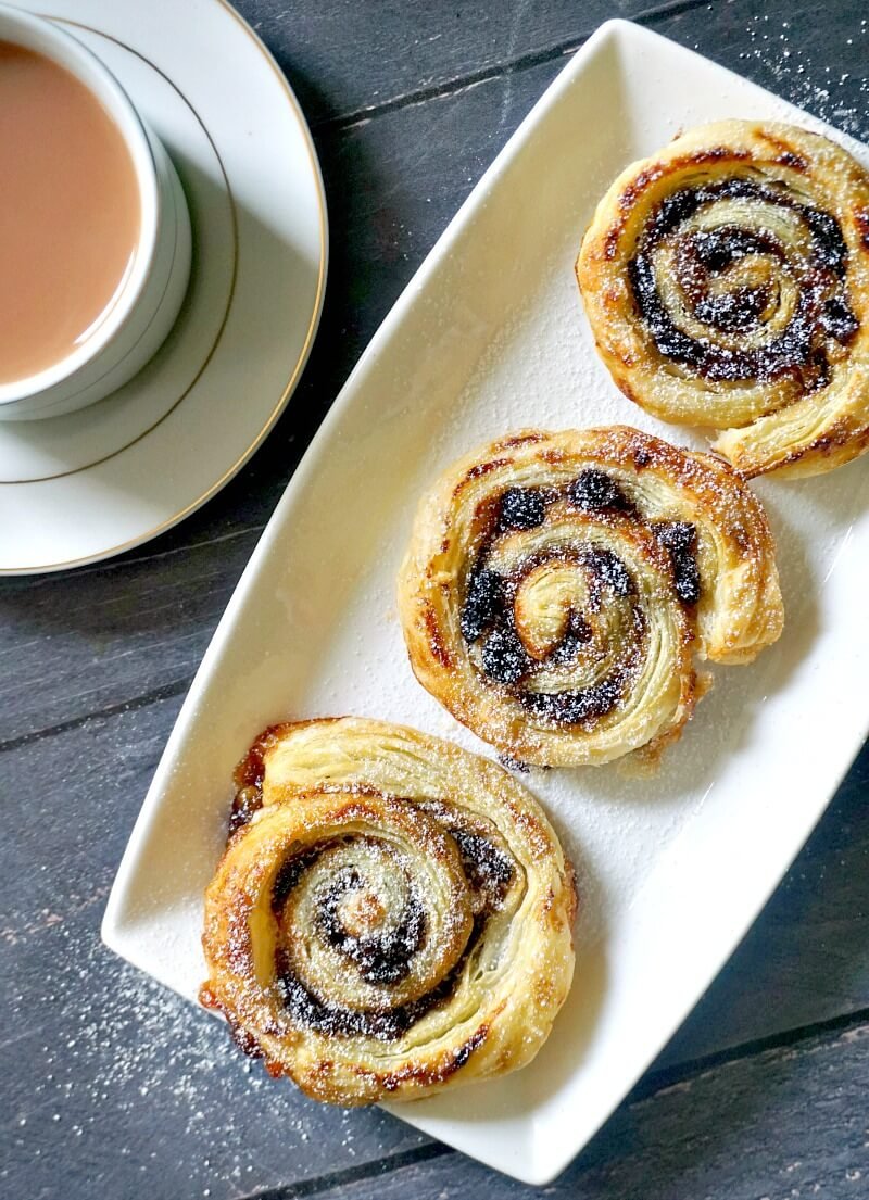 Overhead shoot of a white rectangle plate with 3 mince pie pinwheels and a cup of tea on the side