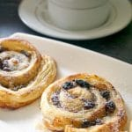 2 mince pie pinwheels on a white rectangle plate with a cup of tea next to it