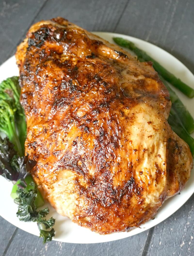 A roast turkey crown on a white plate flanked by green veggies
