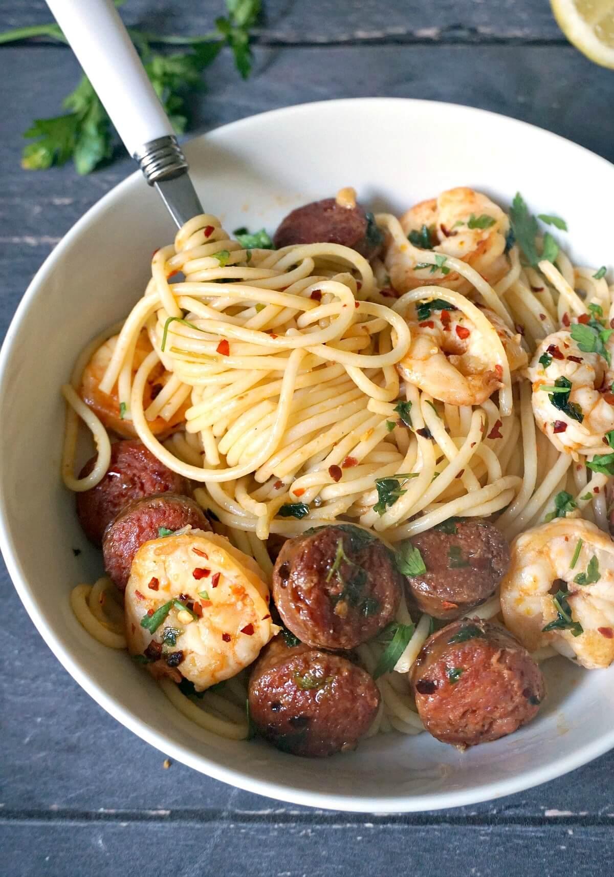 A white bowl with prawn and chorizo spaghetti