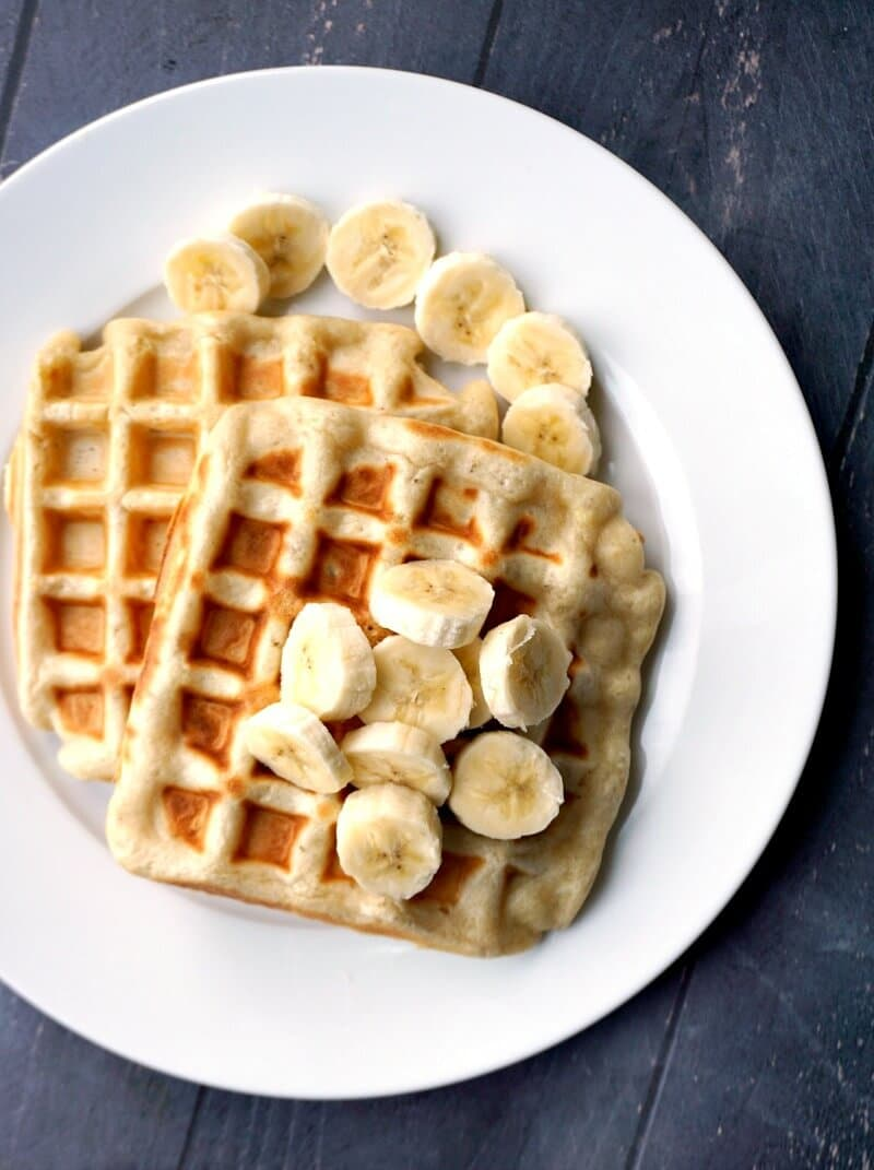 Overehead shoot of a white plate with 2 banana waffles topped with slices of banana