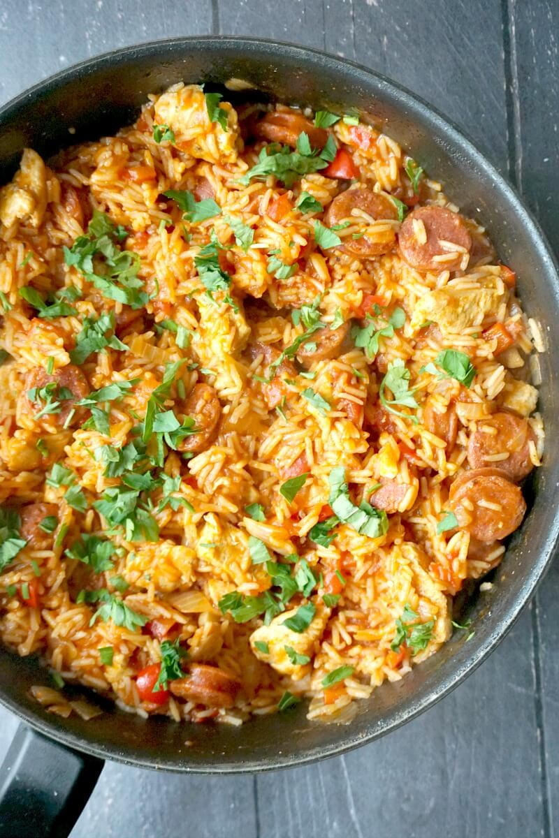 A pan with chicken and chorizo jambalaya garnished with fresh parsley