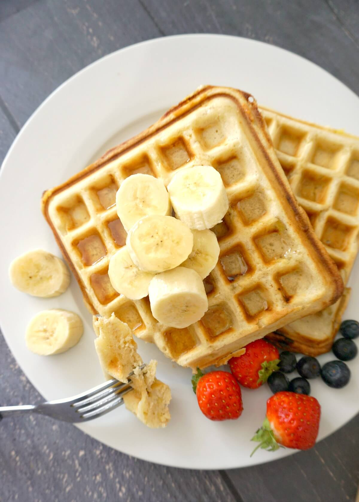2 waffles on a white plate topped with slices of bananas and berries on the side