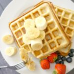 Overhead shoot of a white plate with 2 waffles, banana slices and berries