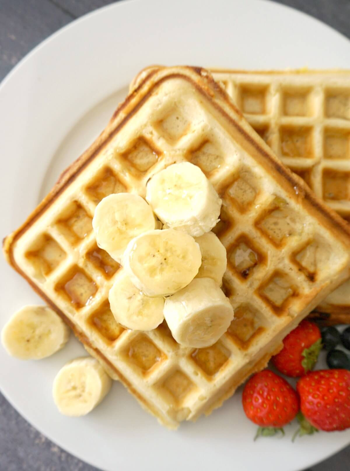 Overhead shoot of 2 waffles on a white plate with slices of bananas around,  3 strawberries and blueberries
