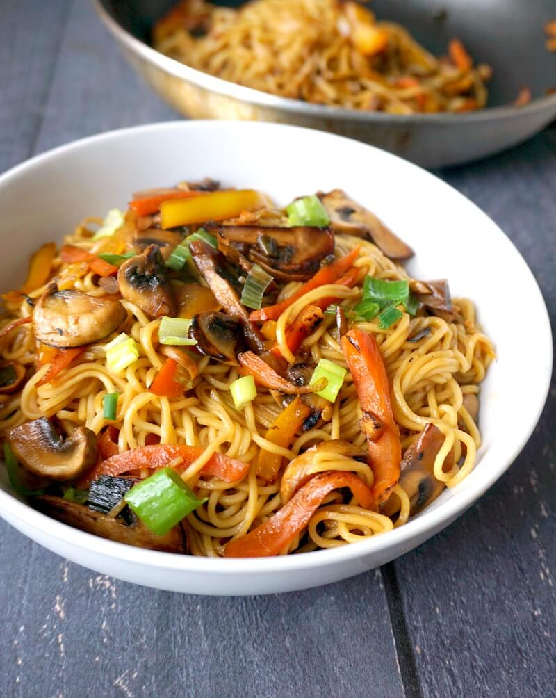 A white bowl with vegetable noodle stir fry and a pan with more noodles in the background