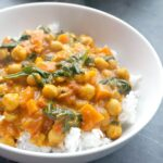 A white bowl with rice and coconut chickpea curry