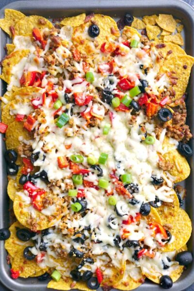 Ground Pork Nachos loaded with mozzarella cheese, olives, red peppers and spring onions, a fantastic party food recipe to feed a crowd. These nachos are not only insanely delicious, but healthy too. Bake in the oven for 5-10 minutes so that the cheese can melt nicely, and you get the best Game Day food. Great for any other celebration too! The ground pork is cooked with garlic and tomatoes, and it goes perfectly well with the tortilla chips. #nachos, #groundporkrecipes, #gameday, #superbowlfood