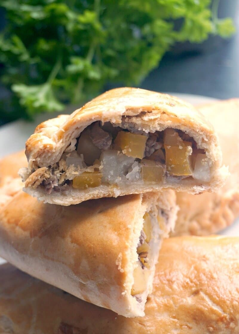 Half of a Cornish pasty on top of other pasties