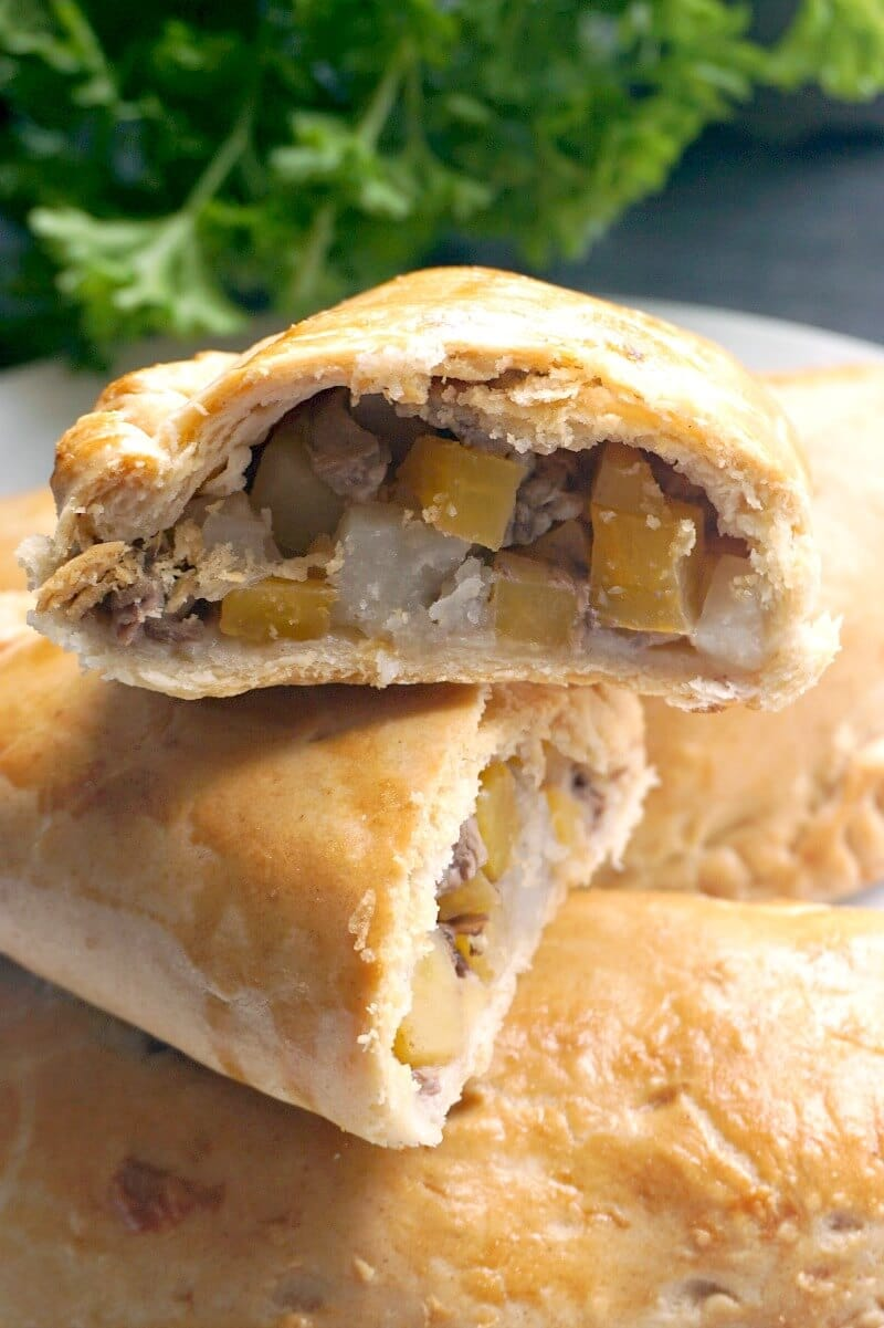 Half of a cornish pasty on top of another half pasty and two whole pasties