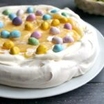 A pavlova topped with cream, lemon curd and chocolate eggs