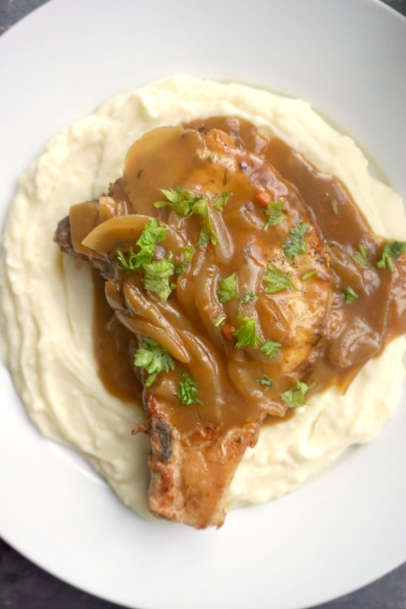 Overhead shoot of a white plate, mash and a pork chop smothered in onion gravy