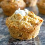 A carrot cake muffin with more muffins in the background
