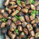 A pan with steak bites and chopped parsley