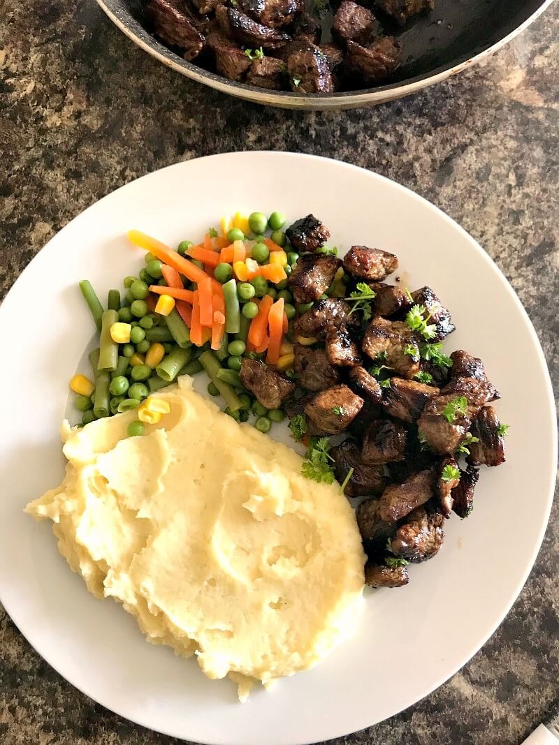 Overhead shoot of a white plate with mashed potatoes, mixed veggies and steak bites