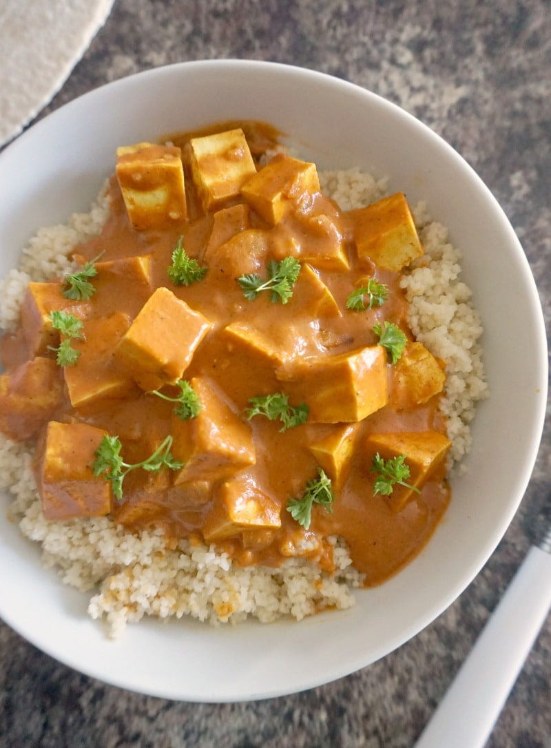 A white bowl of couscous and creamy tofu curry