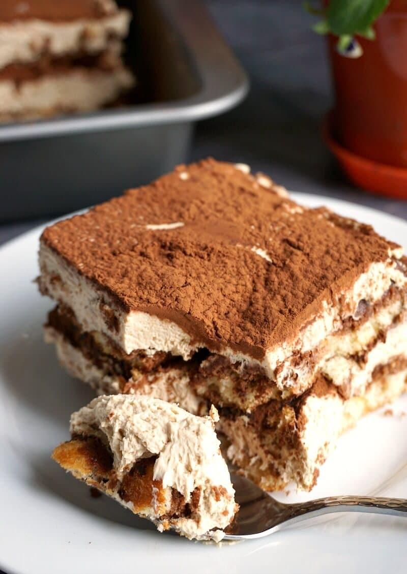 A slice of dalgona tiramisu n a white plate with a teaspoon in