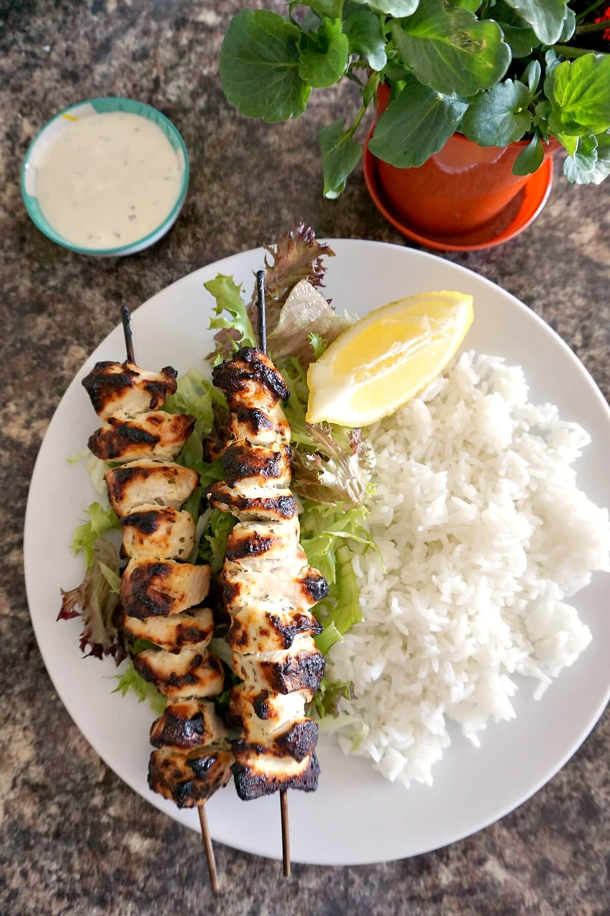 Overhead shoot of a white plate with 2 chicken kebabs, rice, salad and a lemon wedge