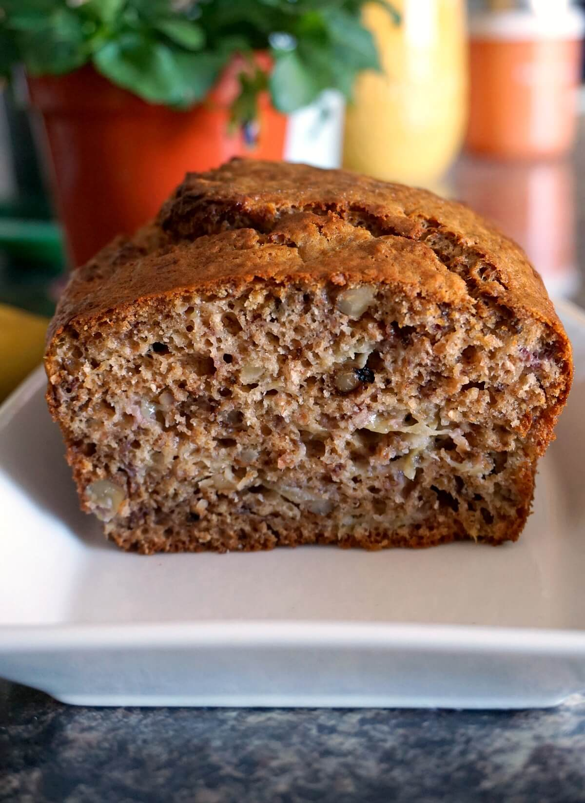 A half banana bread on a white rectangle plate