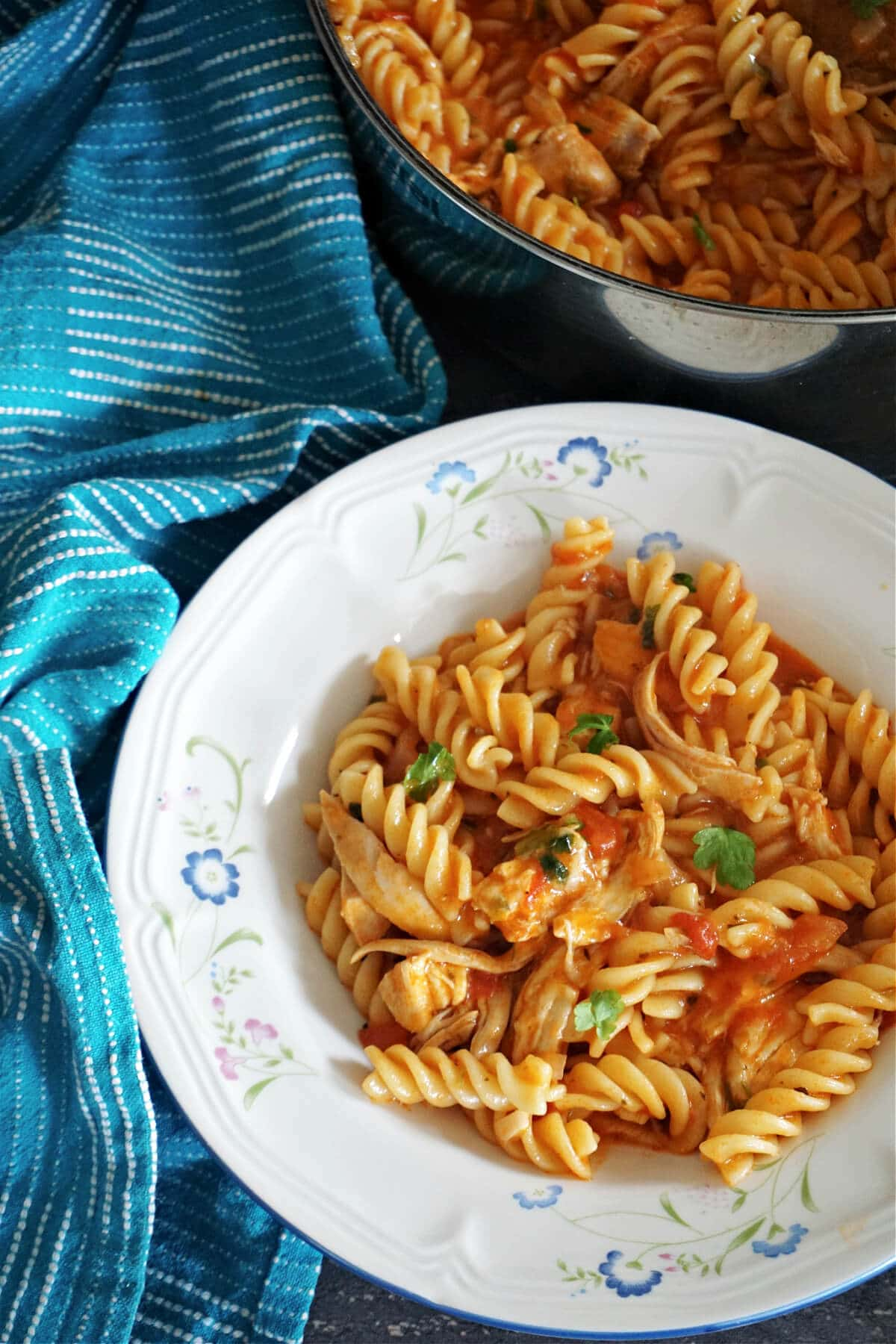 A white plate with pasta with chicken and tomato sauce