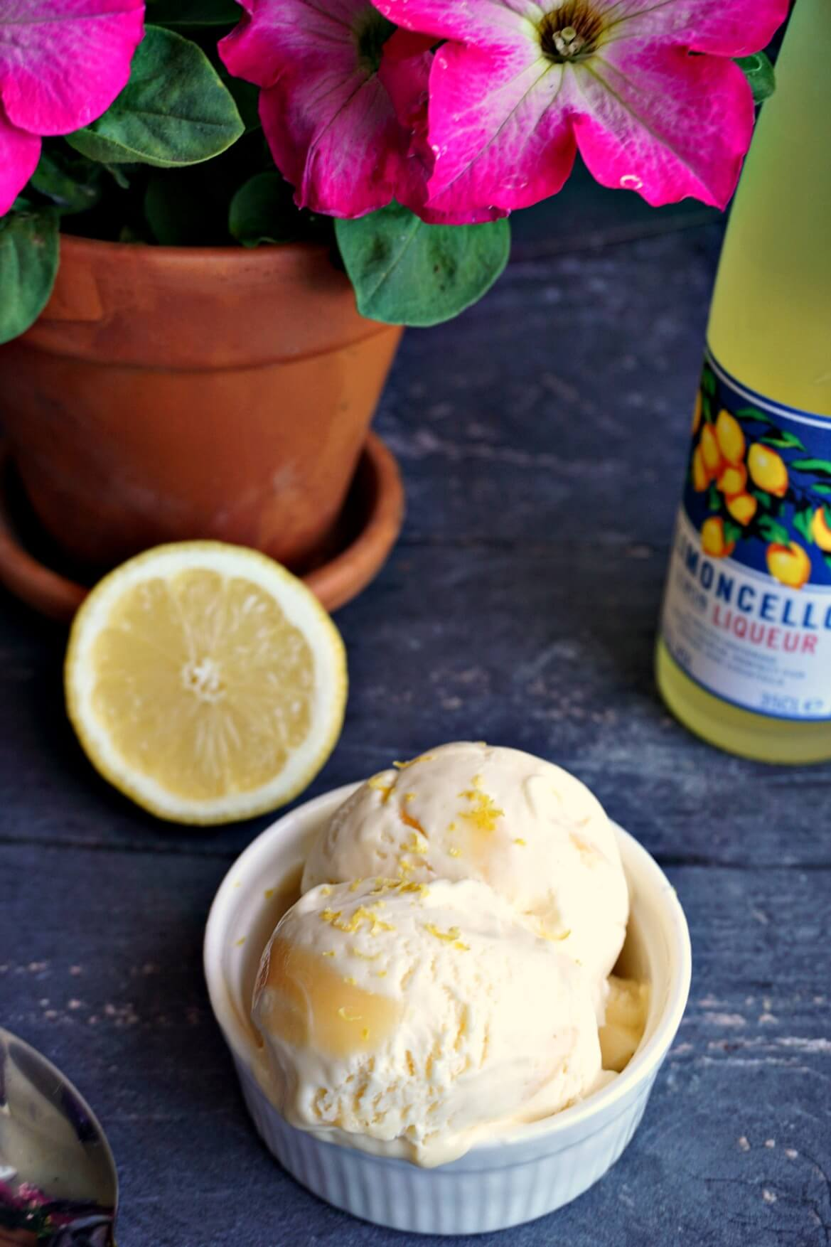 A white bowl with 2 ice cream wcoops, half a lemon, a bottle of limoncello and a pot of flowers